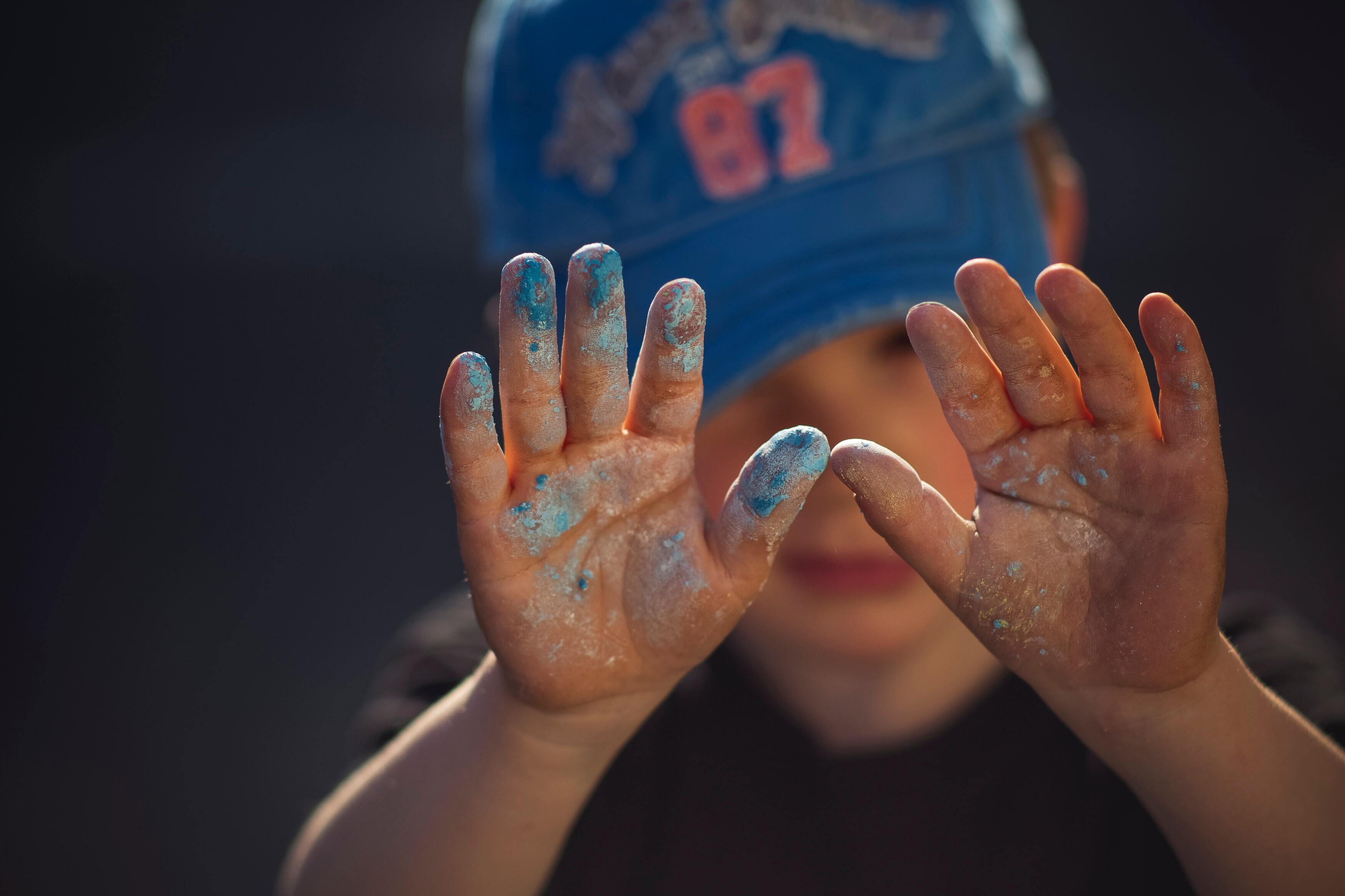 young boy wearing hat with paint on hands