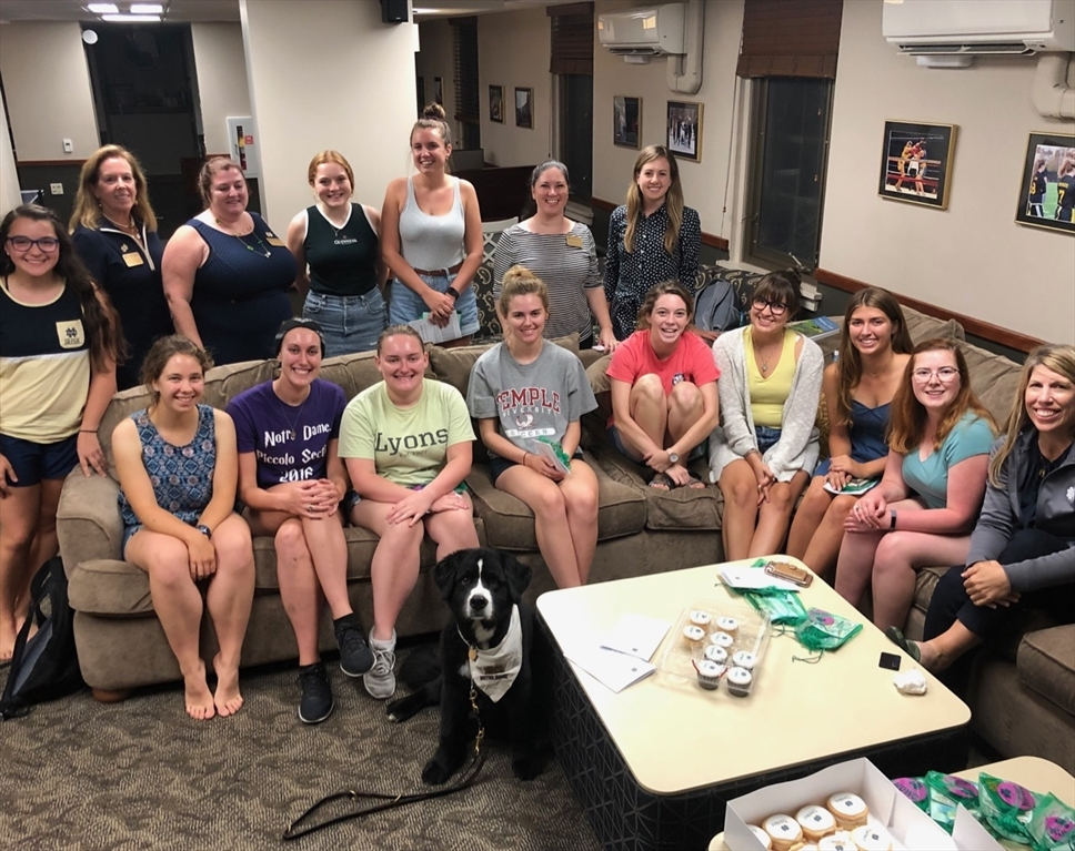 Students and alumnae sit in a dorm lounge.