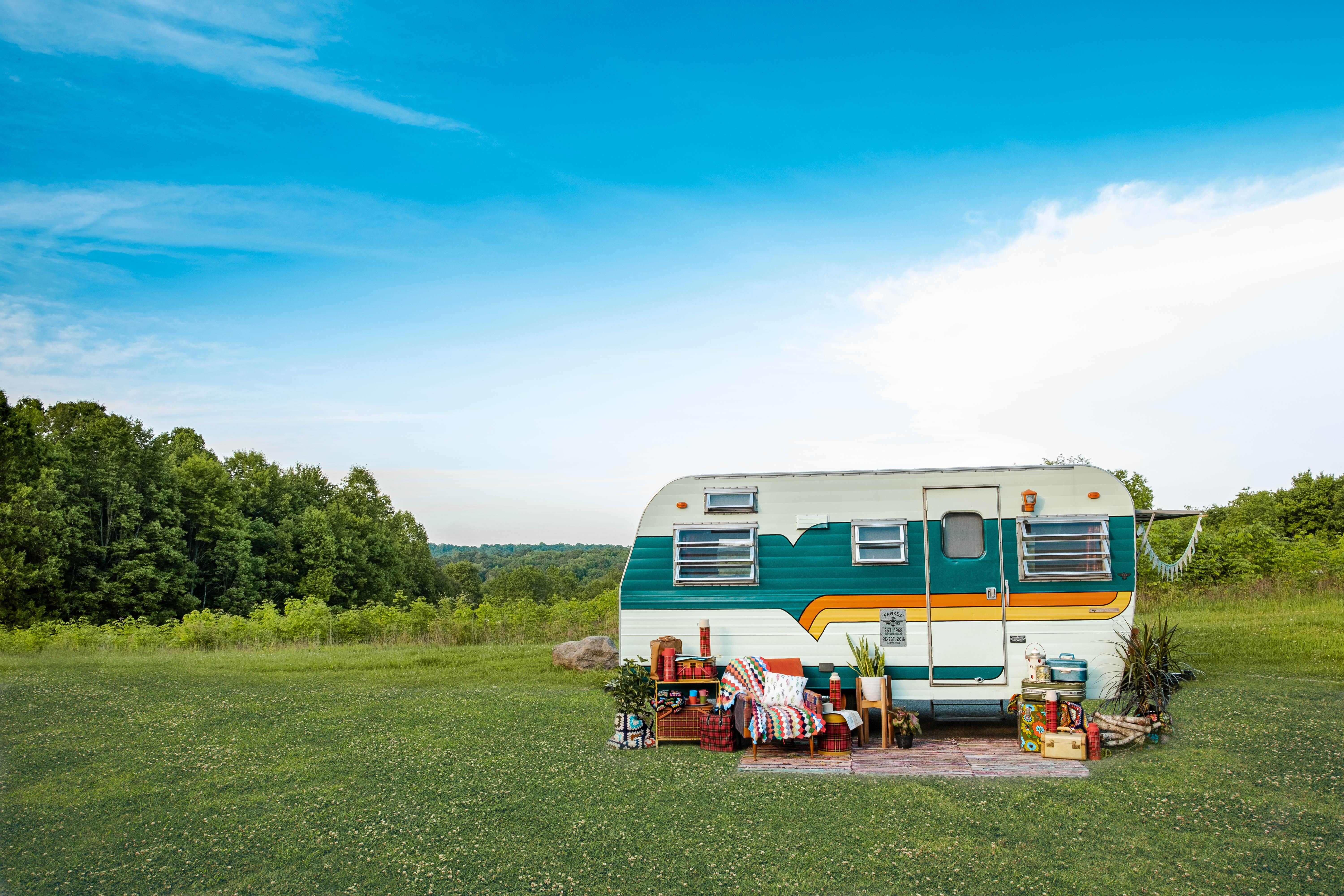 A vintage trailer with a wide turquoise stripe and small orange and yellow stripes sits in the middle of a green grassy clearing with a chair and picnic array sitting at the ready outside its doors.