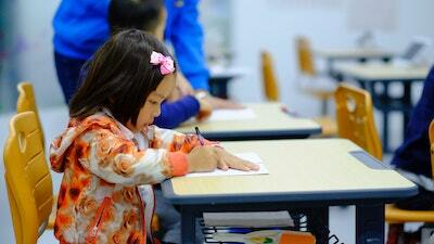 A female elementary school student in a floral-patterned sweatshirt sits at a desk in a classroom and writes on a piece of paper.