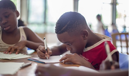 Two Black children sit together at a desk. The child in front has shortly cropped black hair and is wearing a red shirt, looking down at a piece of paper and writing with a pencil.