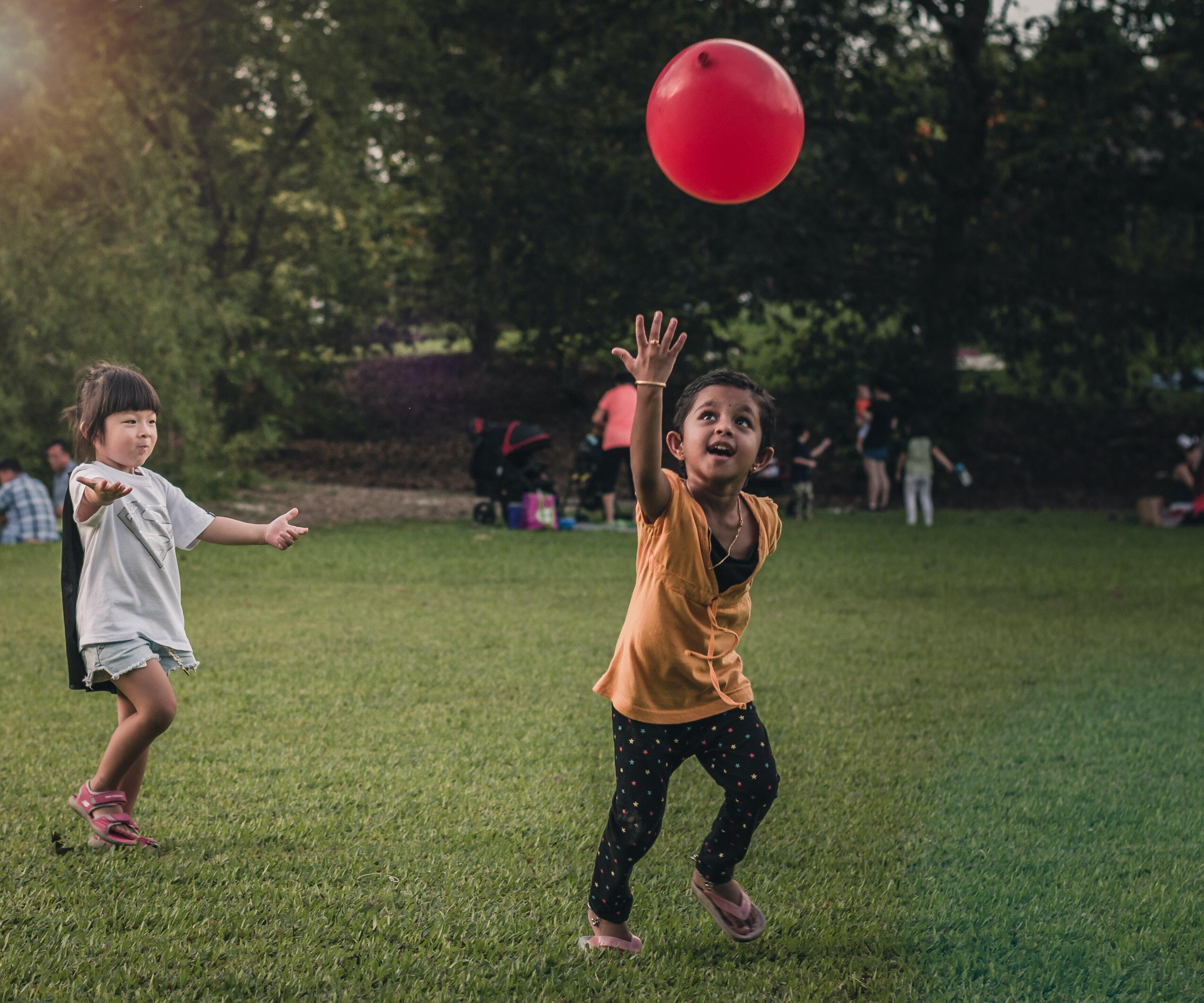 Two young girls, one with bangs and long black hair, one with short black hair and a gold bracelet, play with a red balloon at a grassy green park.