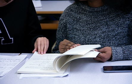 Two people sit at a white desk and look through a booklet.