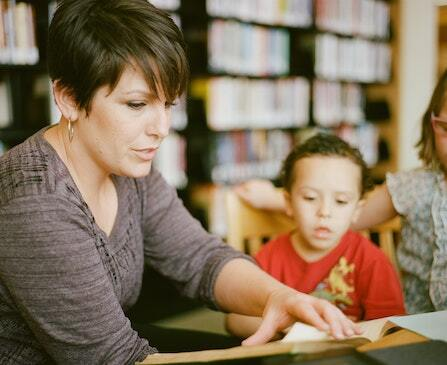A female aide with a brunette pixie cut is sitting at a table with a young boy in a red shirt as they read a book together.