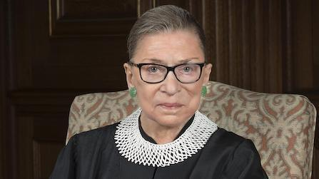 An official portrait of Supreme Court Justice Ruth Bader Ginsburg. Her brown hair is pulled back, she is dressed in a black robe with a white collar, and she is wearing glasses.