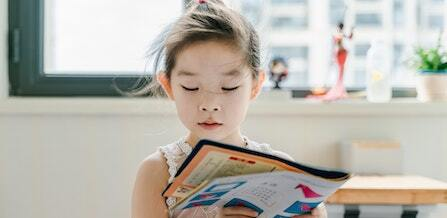 A young female student with her hair pulled back at home reading a book.