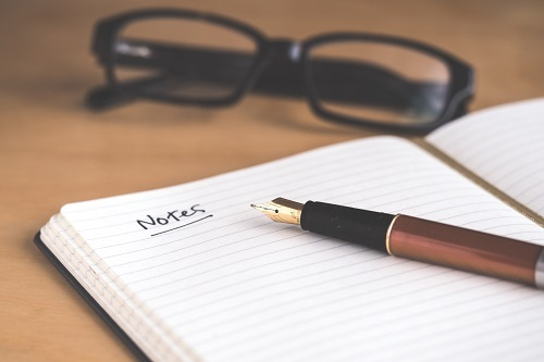A notebook with white lined pages is open on a wooden desk with a calligraphy pen on top; the word Notes is written on the page and underlined. A pair of black-rimmed glasses sits above the notebook.