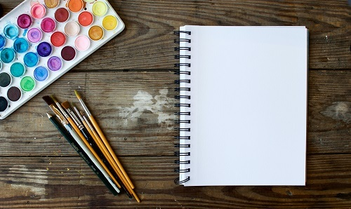A blank white notebook sits on a wood tabletop, with watercolors arranged in the top left and a slew of paintbrushes and one pencil at the bottom.