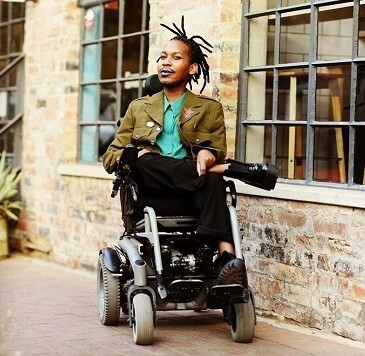 A Black man with dreadlocks and purple lipstick wears an olive green military-style jacket over a turquoise button-up shirt with black pants and boots. He sits in a power wheelchair with one leg crossed over the other in front of a brick building with large windows.
