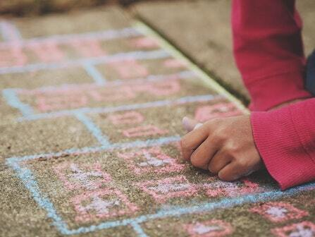 Child wearing a long-sleeve pink shirt drawing with chalk on concrete