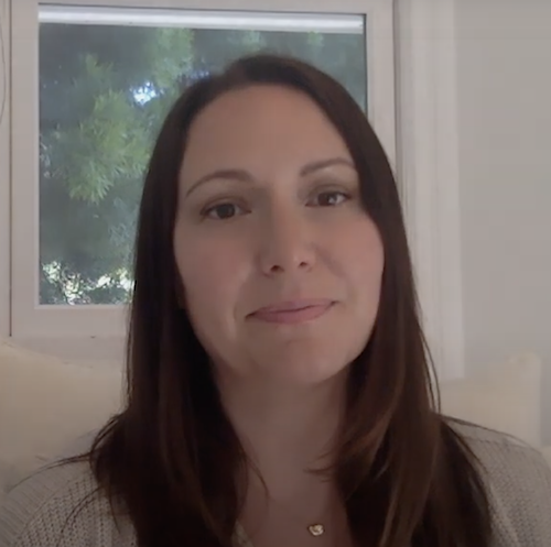 Dr. Lauren Stutman, a woman with long brown hair and brown eyes, sits in front of a window speaking to the camera with a kind expression on her face.