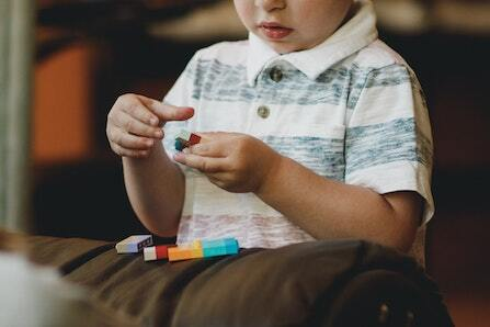 A young boy in a striped T-shirt playing with LEGOS