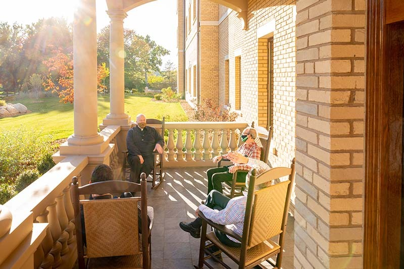 Four men wearing masks sit on the front porch of Corby Hall on a sunny evening.