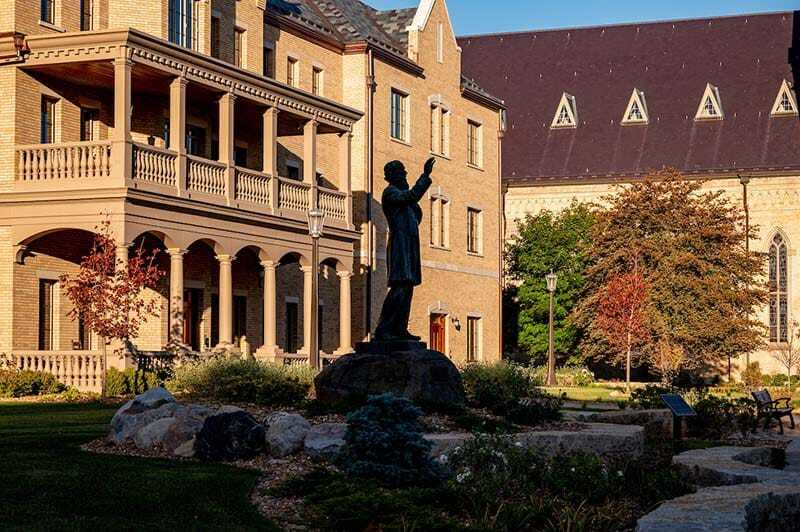 A statue of Fr. Corby in front of Corby Hall on a fall day.