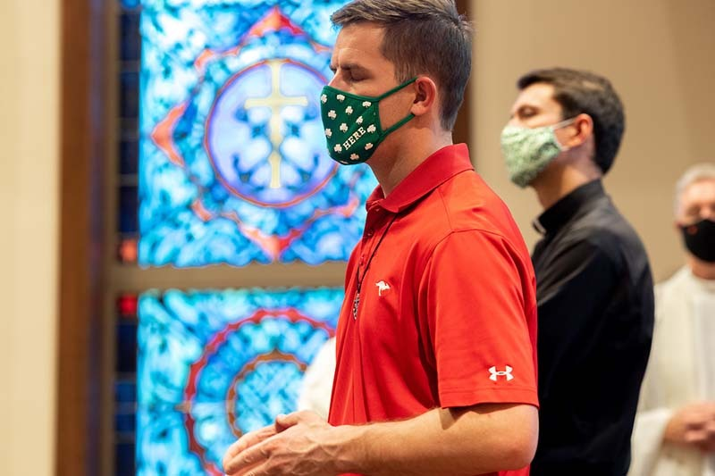 A masked man prays with his eyes closed in the chapel.