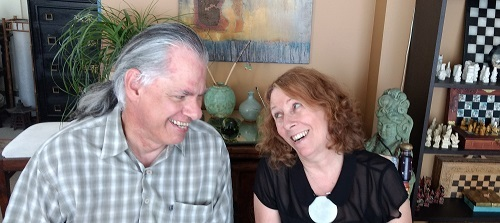A man with silver hair pulled back in a ponytail smiles at a woman with curly red hair as they sit in their living room .