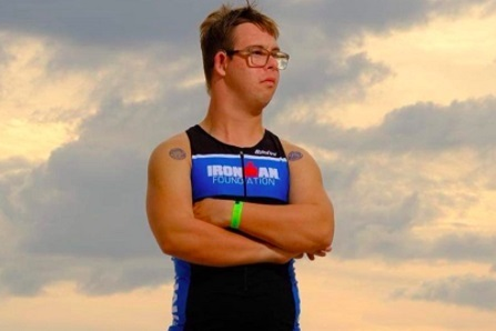 """A white man with short brown hair and glasses looks off into the distance with his arms crossed over his chest. He is wearing a black tank top with """"Ironman"""" printed in white and red letters across a blue stripe. A cloudy sky provides the backdrop."""