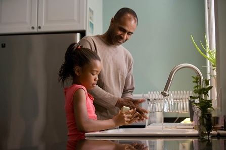 A man stands at the kitchen sink while a child washes her hands