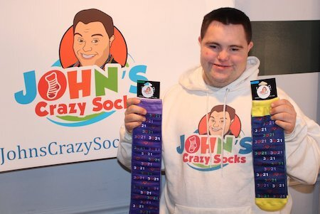 """John Lee Cronin, a white man with short black hair wearing a white hoodie sporting a cartoon drawing of his own face and colorful letters reading """"John's Crazy Socks,"""" stands in front of a poster of the same image. He holds two Downs syndrome awareness socks that read 3 """"heart"""" 21."""