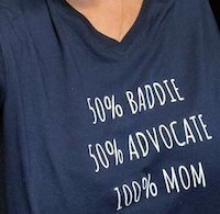 """A navy T-shirt reads """"50% baddie, 50% advocate, 100% mom"""""""