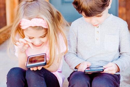 A young boy and young girl sitting on a porch, each each reading from their own smartphones.