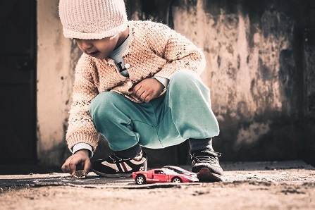 A young child wearing a knit hat, a white sweater, and blue pants crouches while playing with race cars outside.