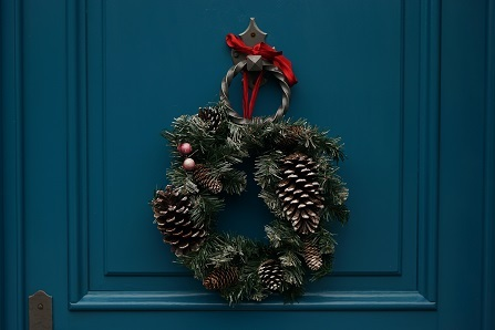 A winter wreath with snowy pinecones is hung from a dark blue door with a red bow.