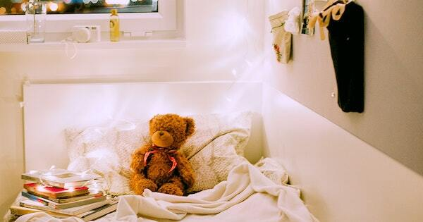 A teddy bear sits against on a white unmade bed next to a stack of books wrapped in lights. City lights are visible through the window, and a stocking hangs next to the bed.