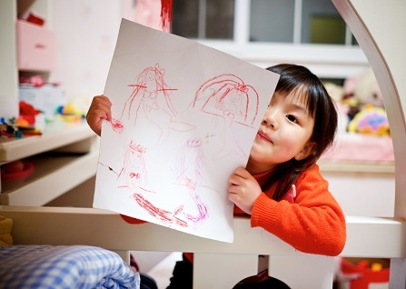 A young Asian child with dark hair and bangs holds up a drawing of a mermaid and smiles