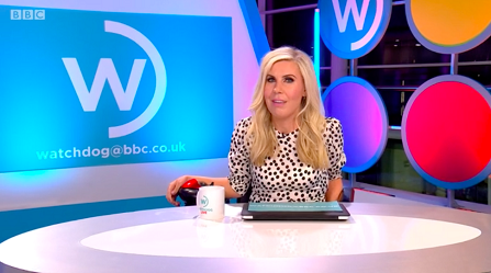 """A white woman with long blonde hair sits in a motorized scooter behind a news desk. She's wearing a black and white polka dot blouse. The blue screen behind her features a white """"W"""" and reads watchdog@bbc.co.uk."""