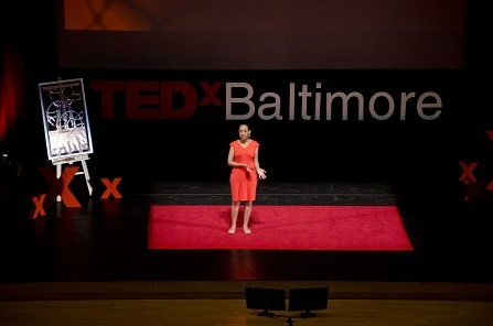 """A woman in a coral dress stands on a red carpet on a stage with the words """"TEDx Baltimore"""" in the background"""