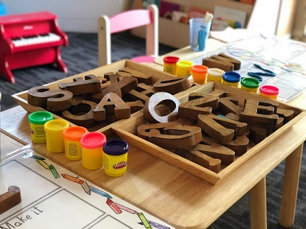 Wooden letters of the alphabet sit in a wooden tray on a table surrounded by jars of Play-Doh