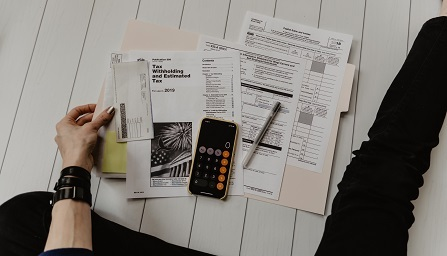 A person wearing black bracelets and black pants sits on the floor with tax preparation documents, a calculator, and a pen