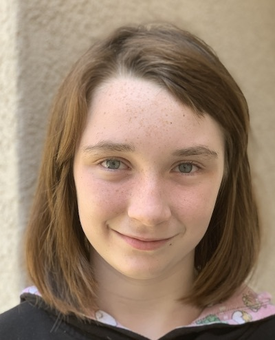 A young freckled girl with blue eyes and dark strawberry blond hair looks fondly into the camera.