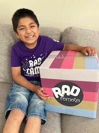 """A young boy who is a RAD Club member wears a purple T-shirt, and sits on a couch next to a striped box that reads """"RAD Remote"""""""