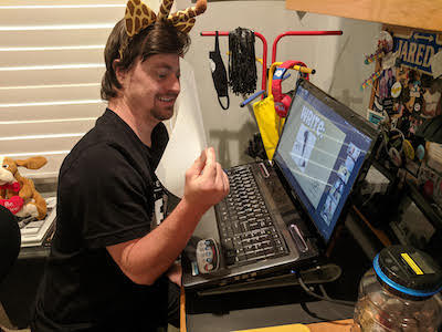 A RAD Club member wearing a black T-shirt and a headband with giraffe ears sits in front of his laptop. A game is on the screen.