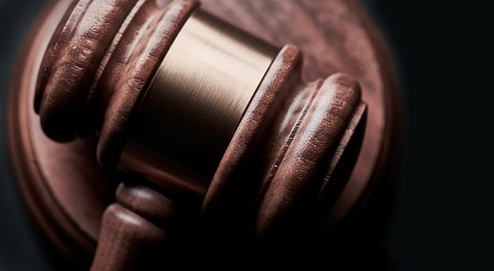 A wooden judge's gavel rests on a circular wooden holder.