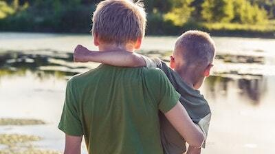 Two brothers wearing green T-shirts, the older with his arm around the younger, stand on a dock looking out at a pond or lake.