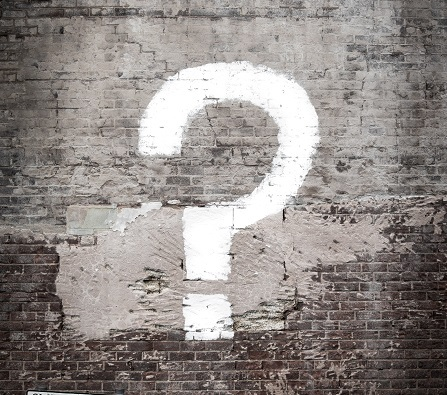 A large question mark is spray-painted in white on a gray brick wall