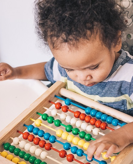 A Black toddler plays with a sliding bead toy