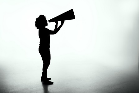 A silhouette of an adult in profile speaking into a megaphone