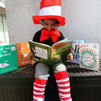 A young African American boy sits in a tall red and white top hat reading a book by Dr. Seuss. He is surrounded by other Dr. Seuss books.